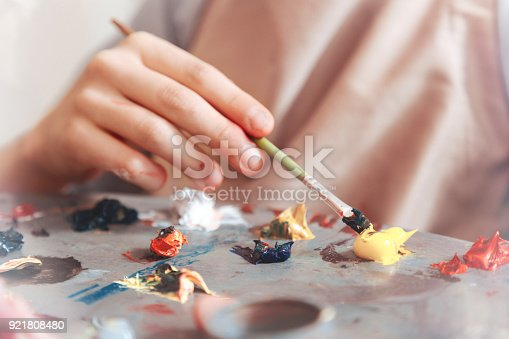 istock Scaled up shot of teenager mixing paints on palette 921808480