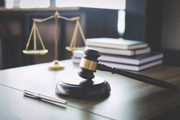 escalas de la justicia y el martillo sobre la mesa de madera y abogado o juez trabajando con contrato en concepto de la sala de audiencias, la justicia y el derecho - abogado fotografías e imágenes de stock
