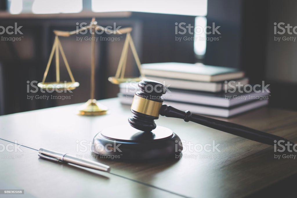 Scales of justice and Gavel on wooden table and Lawyer or Judge working with agreement in Courtroom, Justice and Law concept stock photo