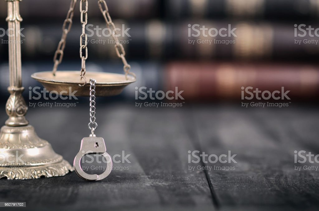 Scales of Justice and handcuffs on a black wooden background. stock photo