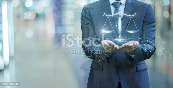istock Scales of justice in the hands of a lawyer . 866706340