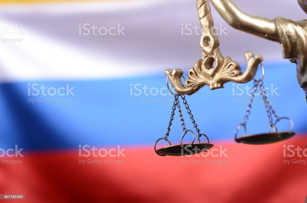 Scales of Justice, Justitia, Lady Justice in front of the Russian flag in the background. stock photo