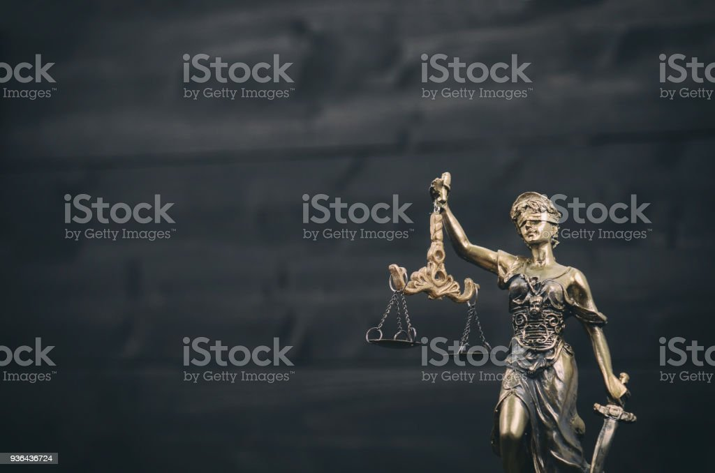 Scales of Justice, Justitia, Lady Justice on a black wooden background. stock photo