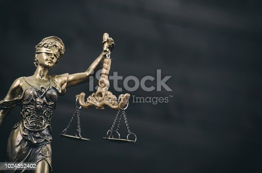 824305956istockphoto Scales of Justice,  Lady Justice on a black wooden background. 1024552402