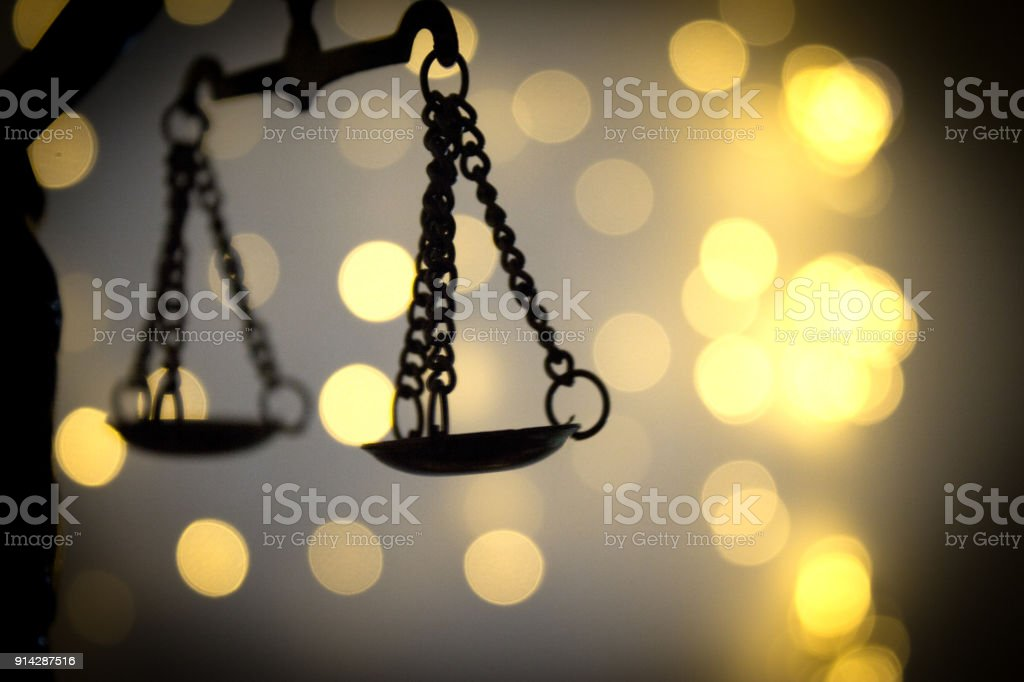 Scales of justice on bright lights background stock photo