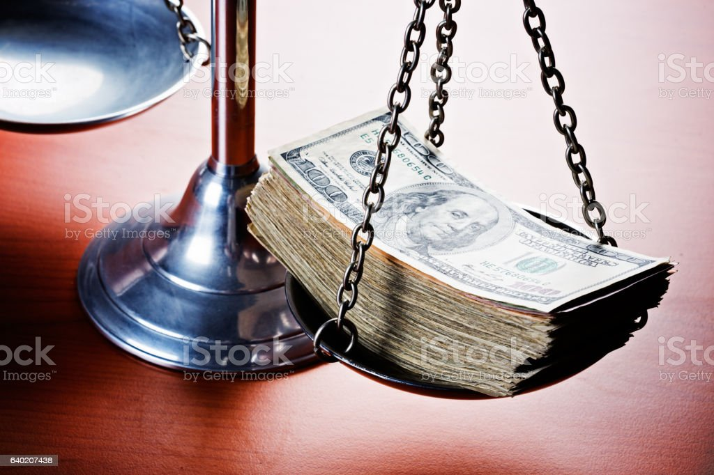 Scales of Justice weighed down by multi-dollar bribe. Corruption! stock photo