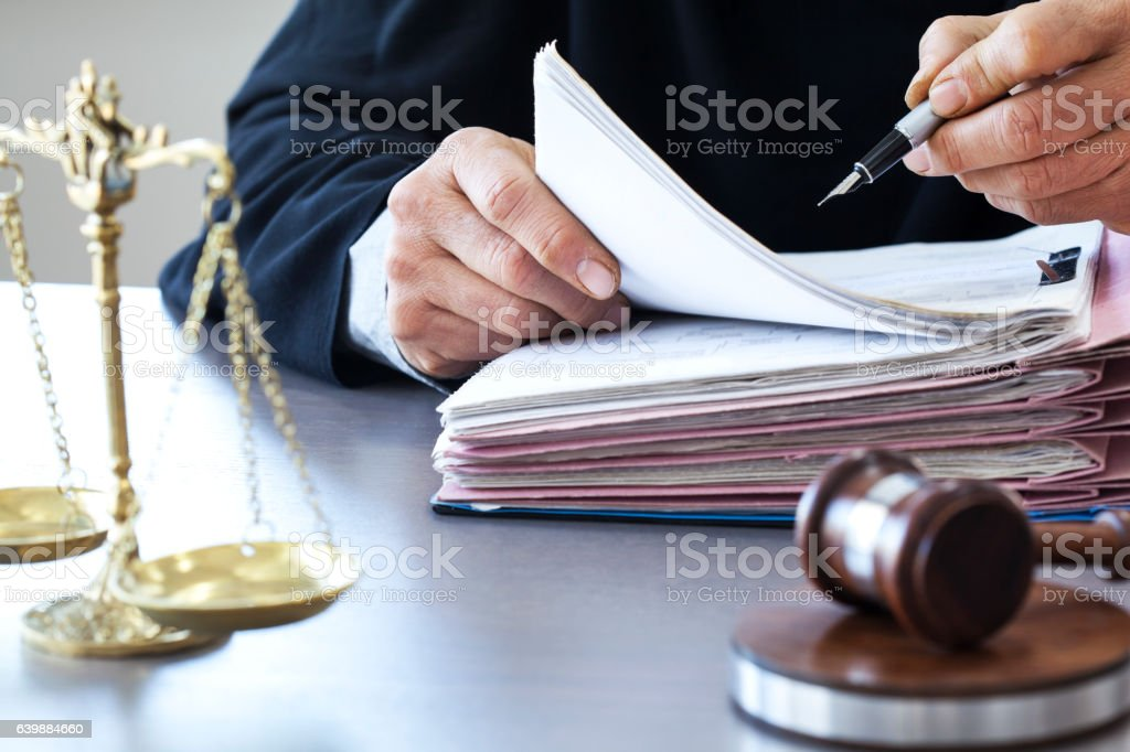 Scales of justice with judge gavel on table stock photo