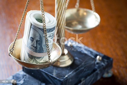 Scales of Justice on wood table with roll of money on pan