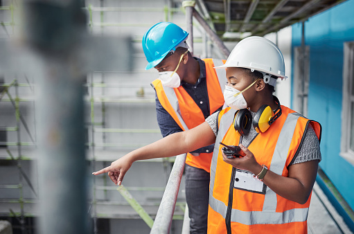 Shot of a young woman using a walkie talkie while working with her colleague at a construction site