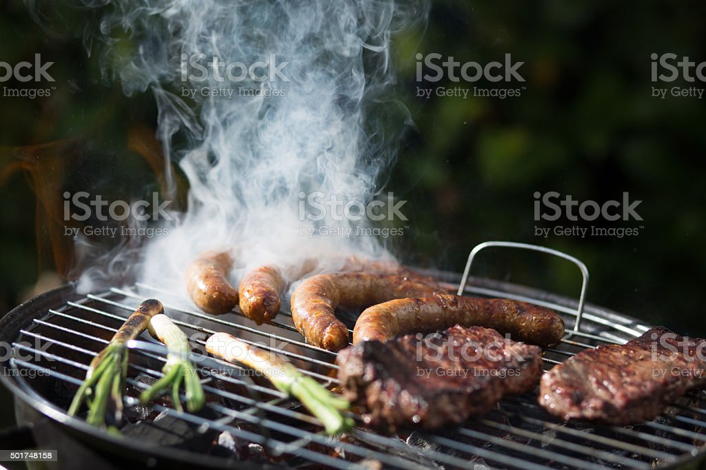 Scallion, sausages and pork on barbecue stock photo