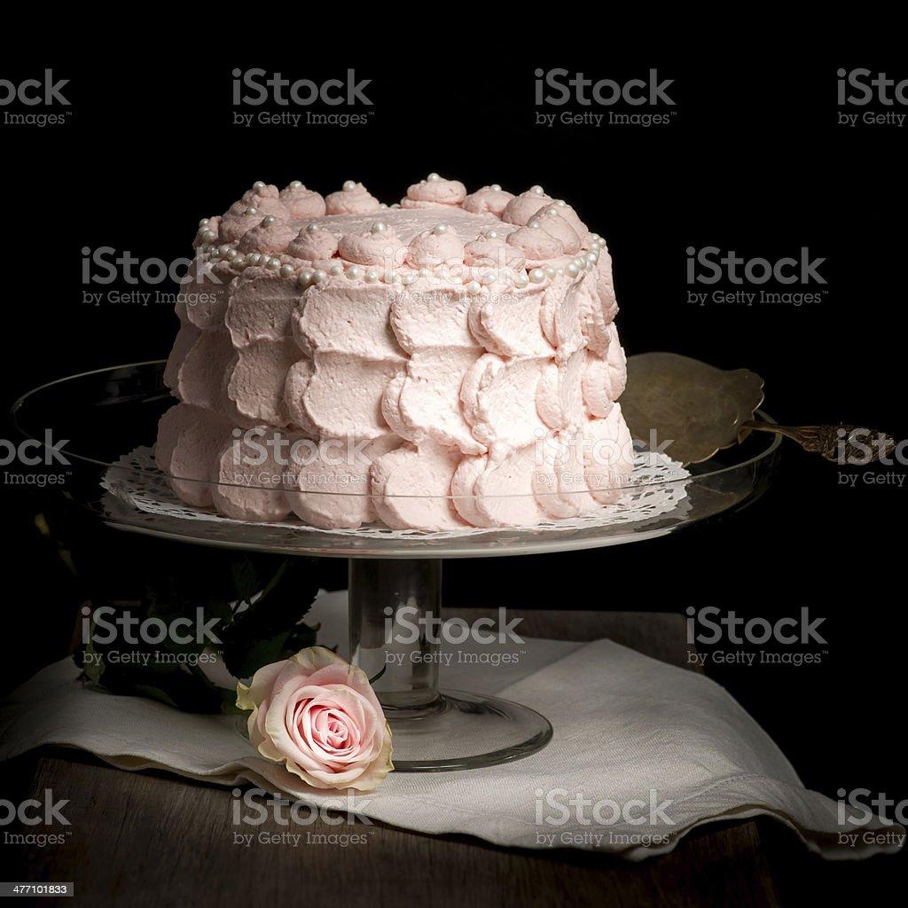 Rundgezackter Zartes Rosa Kuchen auf Glas stand neben rose. – Foto