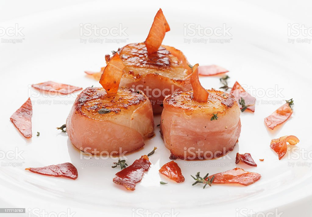 Scallops fried in bacon on plate, close-up stock photo