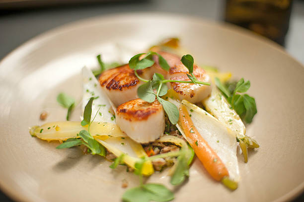 Scallops on a plate with watercress, endive, and baby carrots stock photo