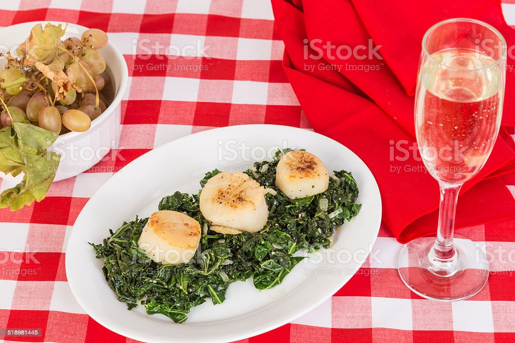 Scallops on bed of Wilted Kale stock photo