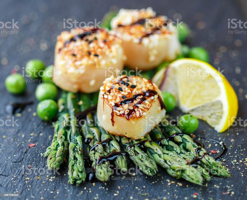 Scallops with sesame seeds, balsamic sauce and  asparagus stock photo