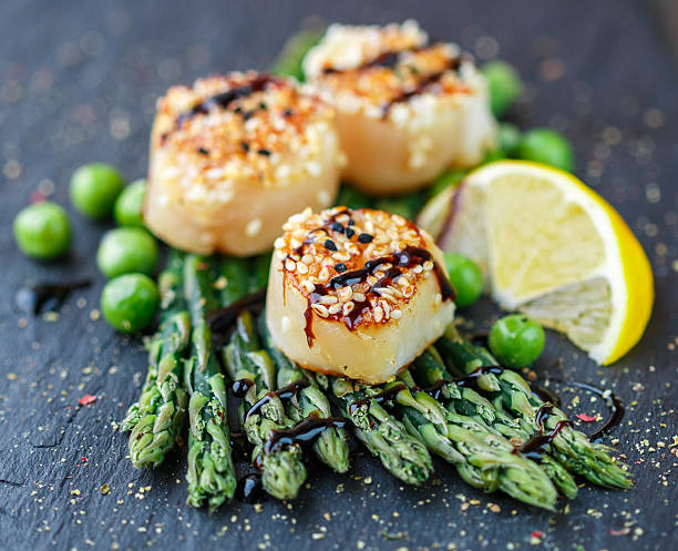scallops with sesame seeds, balsamic sauce and  asparagus - balsamico stockfoto's en -beelden