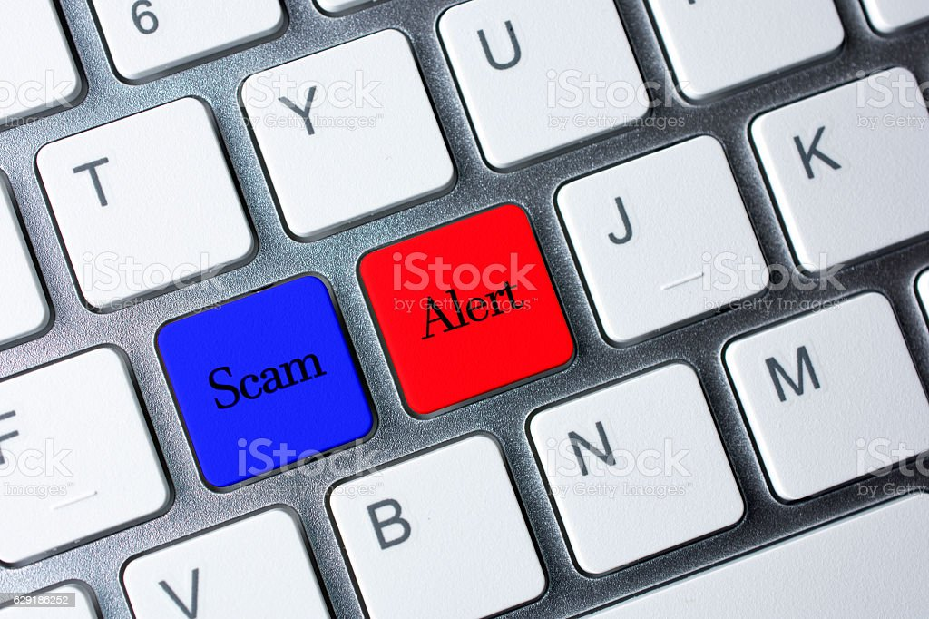 Scam Alert button on white computer keyboard stock photo