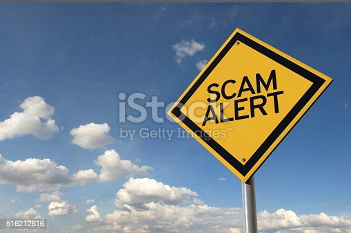 Scam alert yellow highway road sign against summer blue sky with clouds