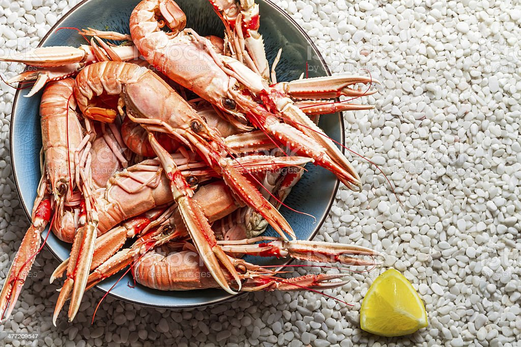 Scampi served with lemon on the beach stock photo