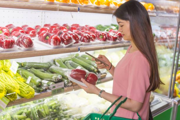 scannen sie barcode auf smartphone, beim kauf von tomaten im supermarkt - kürbis kaufen stock-fotos und bilder