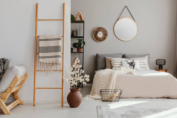 Scandi open space bedroom interior with double bed with knit blanket and many pillows, rack with books and decor, carpet on the floor in real photo stock photo