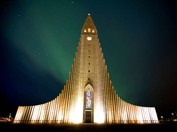 Scandinavian church against the Northern Lights Northern lights  shining over the church in Reykjavik Hallgrímskirkja church stock pictures, royalty-free photos & images