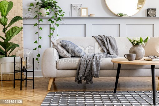 Stylish scandinavian living room interior with design sofa, furniture, tropical plants and decoration. Grey wall. Neutral concept. Template.
