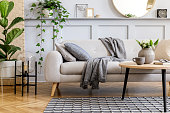 istock Scandinavian concept of living room interior with design sofa, coffee table, plant in pot, flowers, carpet, plaid, pillow, shelf, decoration and personal accessories in modern home staging. 1251694108