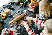 Authentic nordic style series of a real family during Christmas making gingerbread cookies and decorating christmas tree. Home is Scandinavian style log cabin.