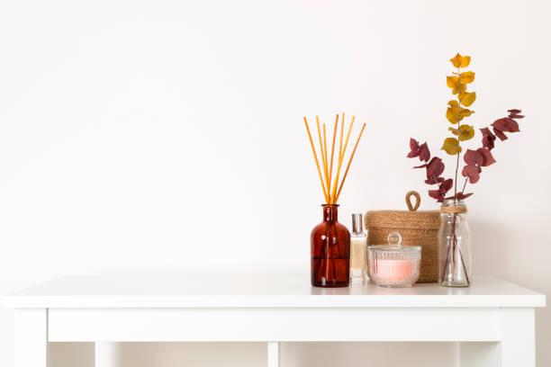 skandynawski styl hygge, wnętrze domu - dyfuzor aromatyczny z drewnianymi pałeczkami, kosz słomy, suszone gałęzie eukaliptusa - perfumowany zdjęcia i obrazy z banku zdjęć
