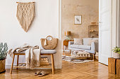 istock Scandinavian interior of open space with wooden bench, grey sofa, pillows, palid, picture frame, macrame, plant, books, carpet, decoration and elegant personal accessoreis in stylish home decor. 1221628549