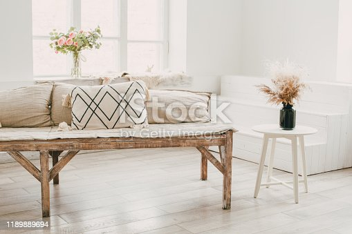 665910118istockphoto Scandinavian minimalist student room design with natural wood furniture and cotton pillows, a white table 1189889694