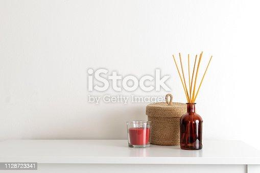 istock Scandinavian nordic hygge style, home interior - candle, scent aroma diffuser, small straw basket, white shelf 1128723341
