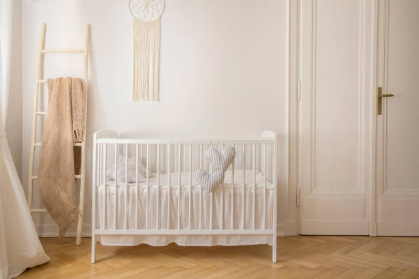 Scandinavian nursery with white wooden crib and macrame on the wall in tenement house, real photo with copy space stock photo