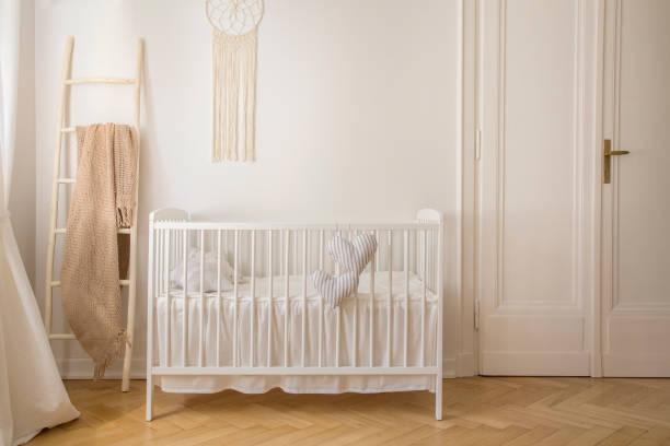 Skandinavische Kinderzimmer mit weißen hölzernen Krippe und Makramee an der Wand im Mietshaus, echtes Foto mit Textfreiraum – Foto