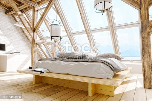 Interior of a Scandinavian style attic bedroom with beautiful sea and mountain view.