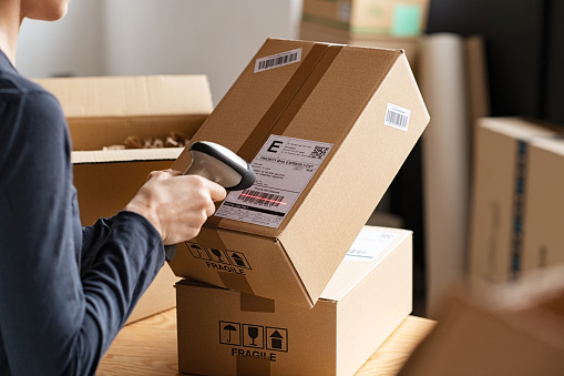 Hands of young woman scanning barcode on delivery parcel. Worker scan barcode of cardboard packages before delivery at storage. Woman working in factory warehouse reading and scanning labels on the boxes with bluetooth barcode scanner.