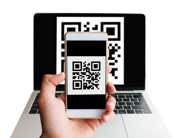 Scanning QR code forn laptop using mobile smartphone stock photo
