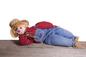 Scarecrow laying down on old wood  in a model pose.