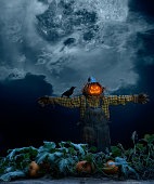 A scarecrow wearing denim overalls stuffed with straw, a glowing Jack O' Lantern as a head, standing in a pumpkin patch at night with the full moon showing through the clouds. There is also a crow with red eyes on the scarecrow's arm.