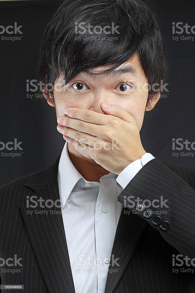 scared adult man with hand covering mouth stock photo