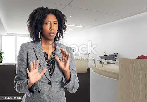 Black African American businesswoman in an office looking scared.  She is an owner or an executive of the workplace.  Depicts careers and startup business.