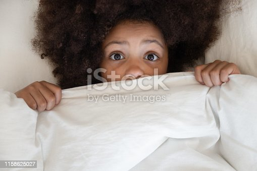 Scared cute little african kid girl looking at camera lying in bed cover with blanket, surprised small black child peeking from duvet wake from bad dream sleep feel fear afraid of nightmare, top view