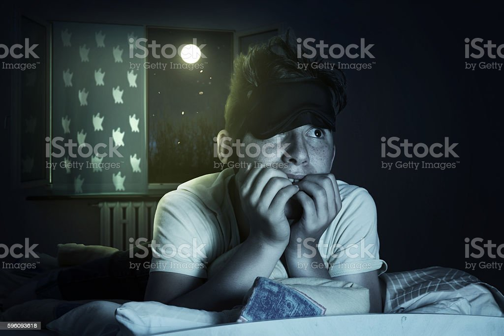 scared and sleepless boy chewing fingernails at bedroom in front royalty-free stock photo
