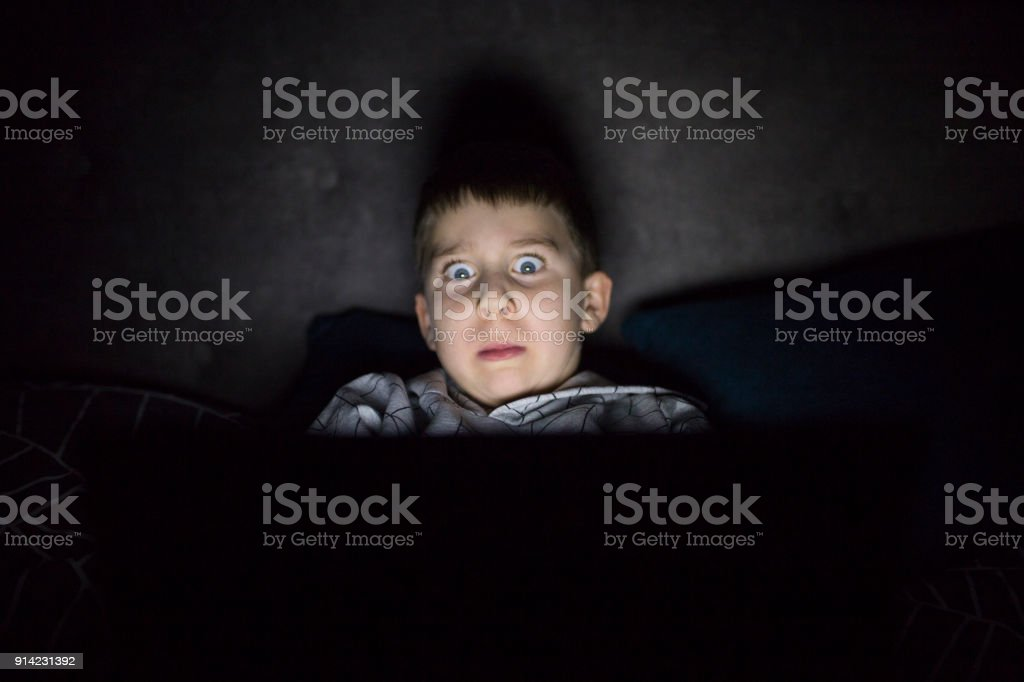 Scared and sleepless boy in bedroom stock photo