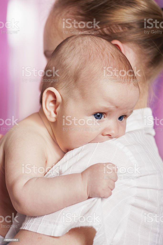 Scared baby in mother's arms stock photo