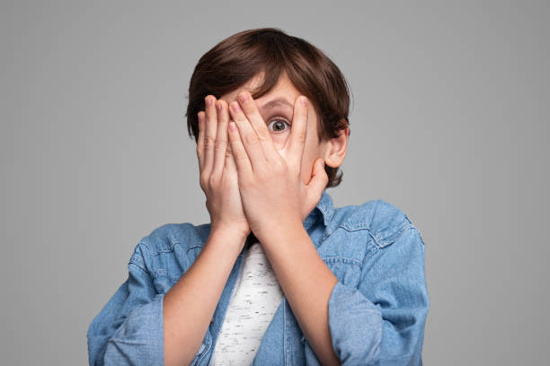 Scared boy covering face stock photo