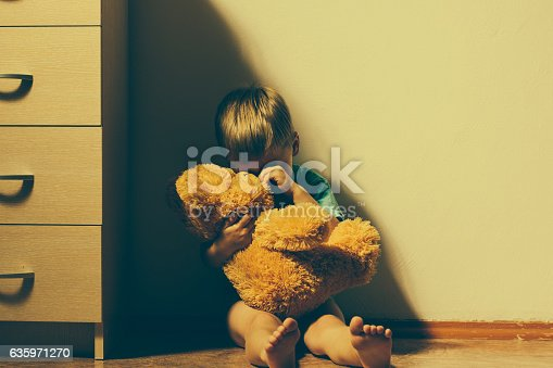 istock Scared boy hugging his teddy bear and crying 635971270