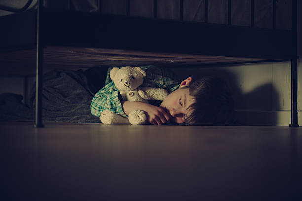 ängstliche junge schlafen unter dem bett mit teddybär - bett für jungs stock-fotos und bilder