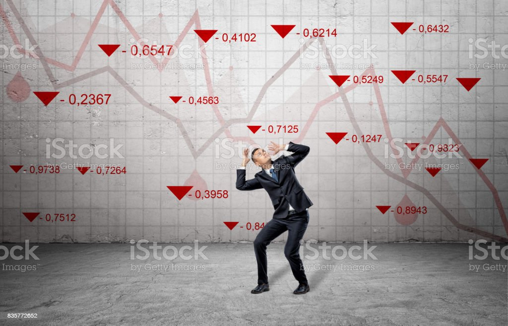 A scared businessman cowers near a concrete wall with red stock market indexes and falling statistic lines stock photo
